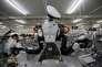 Un robot travaille à côté d'humains dans une usine de Kazo au Japon le 1 juillet 2015.