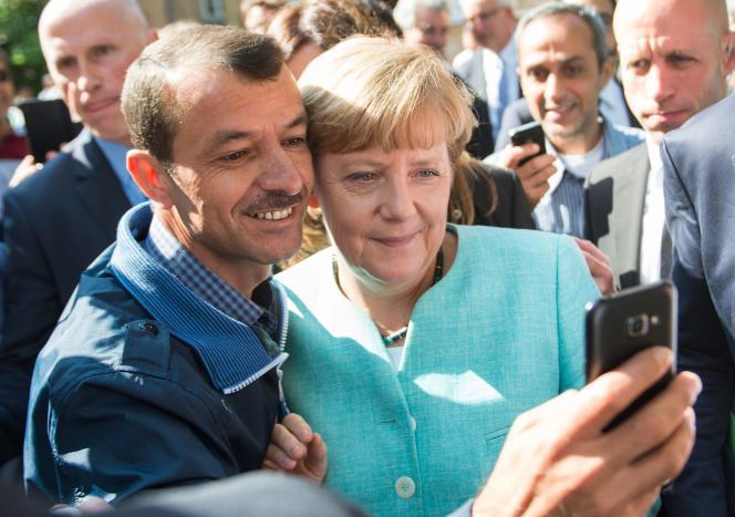 Un demandeur d'asile demande à Angela Merkel de poser avec lui pour un selfie, le 10 septembre 2015 à Berlin.