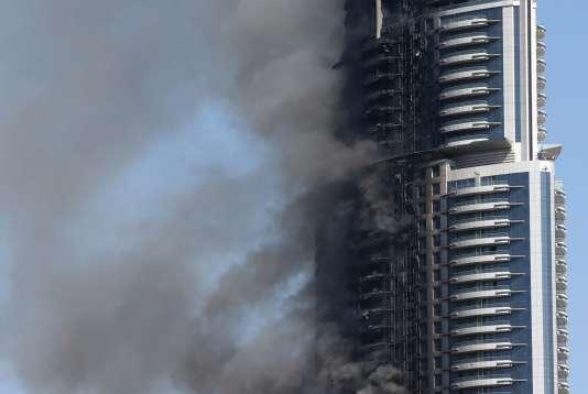 Des panaches de fumée continuent de s'échapper de l'hôtel de luxe qui a pris feu le 31décembre2015 à Dubaï.