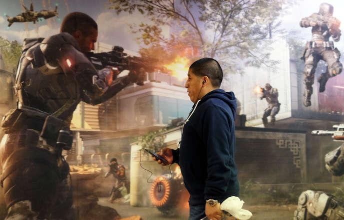Un homme passe devant une affiche de promotion pour le jeu vidéo