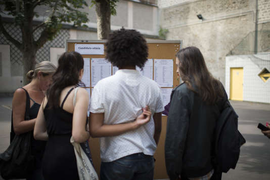 Des élèves regardent les résultats du baccalauréat dans un lycée parisien en juillet 2015.