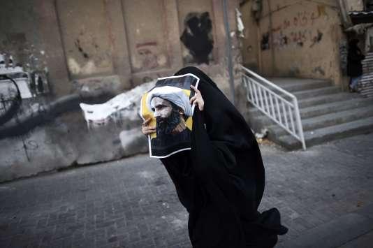 Une femme brandit un portrait du cheikh Al-Nimr lors d'un rassemblement dans le village de Jidhafs à Bahrein, le 3 janvier 2016.