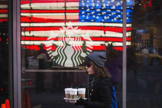 Une cliente transporte des gobelets de café dans un Starbucks de Manhattan à New York en janvier 2014.