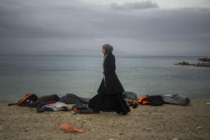 Une femme devant des gilets de sauvetage utilisés par des migrants pour se rendre en Europe, sur l'île grecque de Lesbos, le 5 janvier 2016.