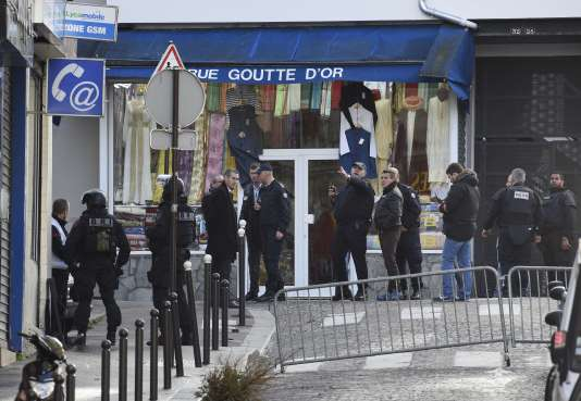 French criminal police are seen in the Rue de la Goutte d'Or in the north of Paris on January 7, 2016, after police shot a man dead as he was trying to enter a police station