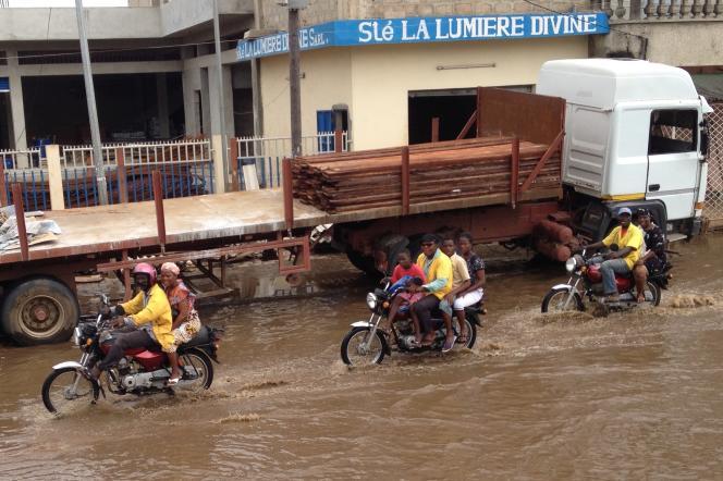 Zémidjans et leurs passagers, dans une rue inondée de Cotonou en juin 2015