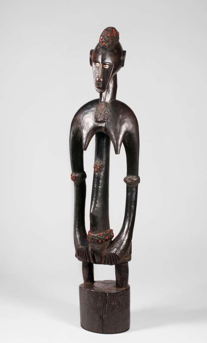 Artiste non identifié, figure féminine, bois, cauris, graines de pois rouges, latex, hauteur : 90,5 cm.