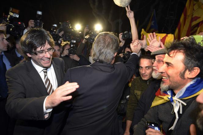 Le nouveau président de la Catalogne, Carles Puigdemont (à gauche), salué par des partisans de l'indépendance, le 10 janvier, à Barcelone.