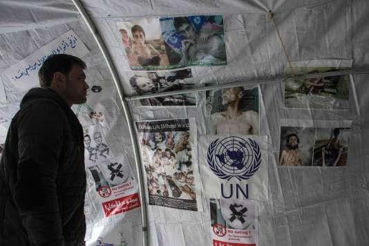 Un Syrien regarde des photos affichées dans une tente, à Alep, le 10 janvier, lors d'une manifestation en soutien aux habitants de Madaya.