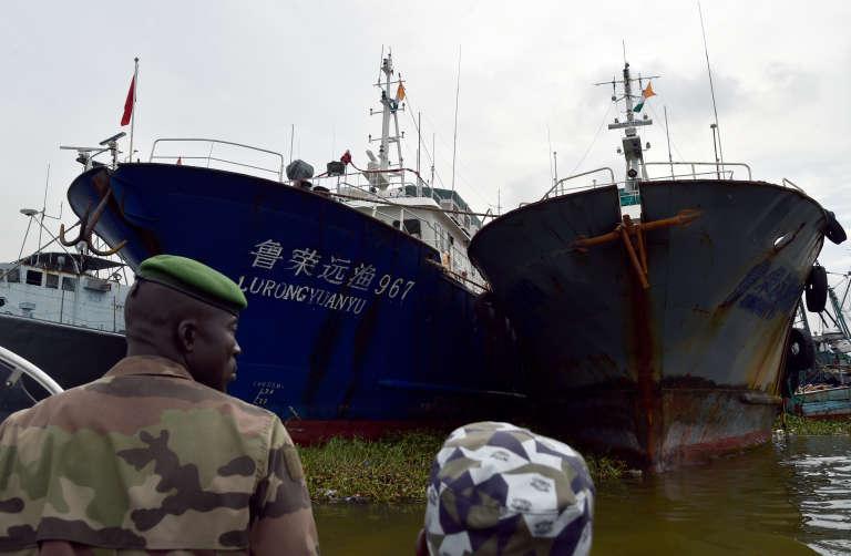 Garde-côtes ivoiriens au port d'Abidjan, où mouillent des chalutiers de pêche chinois en novembre 2014.