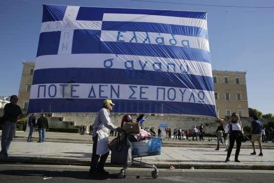 """Un vendeur ambulant marche devant un drapeau grec sur lequel il est écrit : """"La Grèce, on t'aime. On ne te vendra jamais"""". Sur la place Syntagma, au pied du Parlement grec à Athènes, le 22 novembre."""