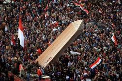 En Egypte, des manifestants portent une obélisque sur laquelle sont inscrits les noms des victimes de la révolution de 2011, le 25 janvier 2012.