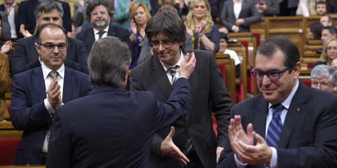 Artur Mas (de dos), président du gouvernement sortant, félicite Carles Puigdemont, maire de Gérone, pour son investiture à la tête du gouvernement catalan, le 10 janvier 2016 à Barcelone.