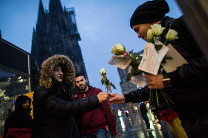 Des membres d'une association germano-tunisienne distribuent des fleurs aux passants devant la gare de Cologne, le 7 janvier.