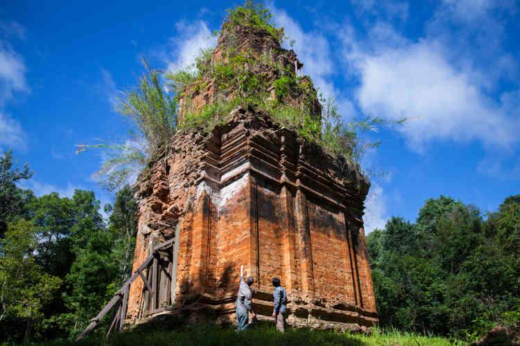 Les archéologues Jean-Baptiste Chevance et Sakada Sakhoeun posent devant le temple O'Paong (IXe-Xe siècles). Dédié au dieu Vishnu, divinité du panthéon hindou que les anciens khmers vénéraient, il a été débarrassé de sa gangue végétale.  La statue du dieu est au musée de Phnom Penh.