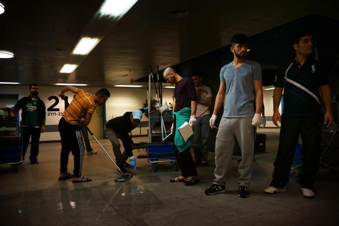 Des migrants participent aux tâches ménagères dans un hôpital transformé en centre d'accueil à proximité d'Elseneur, le 12 janvier 2016.