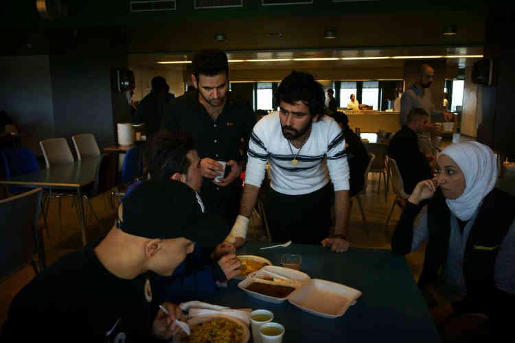 Des réfugiés discutent après le repas.