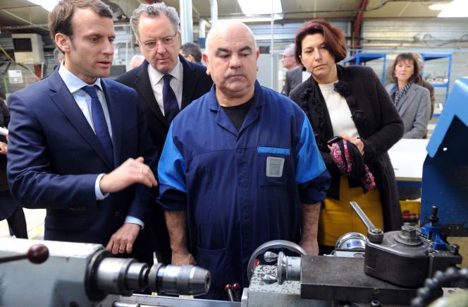 Emmanuel Macron, ministre de l'économie, de l'industrie et du numérique, avec Richard Ferrand, député du Finistère et Nathalie Sarrabezolles, présidente du conseil départemental du Finistère, dans une usine à Pleyben (Finistère), le 15 janvier. FRED TANNEAU / AFP