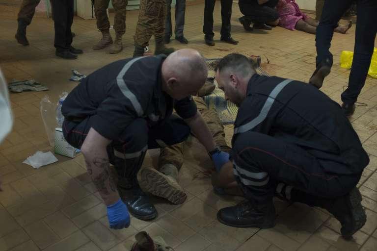 Des pompiers français assistent un blessé à proximité de l'hôtel Splendid, à Ouagadougou, le 15 janvier 2016.