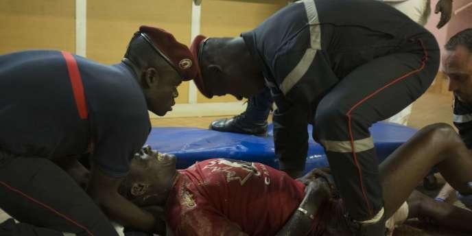 Des pompiers prennent en charge un blessé, à Ouagadougou, dans la nuit du 15 au 16 janvier.