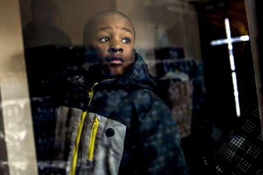 Jaiden Ellis, un jeune habitant de Flint (Michigan), âgé de huit ans, observe la distribution d'eau potable dans une église de la ville, pendant une réunion publique, le 17 janvier.