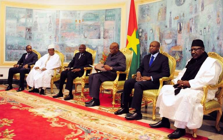Plusieurs ministres burkinabé et malien entourent le président du Burkina Faso, Roch Marc Christian Kaboré (au centre), le 17 janvier 2016, au palais présidentiel de Ouagadougou.