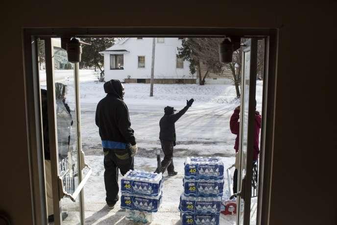 Des volontaires distribuent des bouteilles d'eau minérale à la sortie d'une église de Flint, dans le Michigan, le 11 janvier 2016.