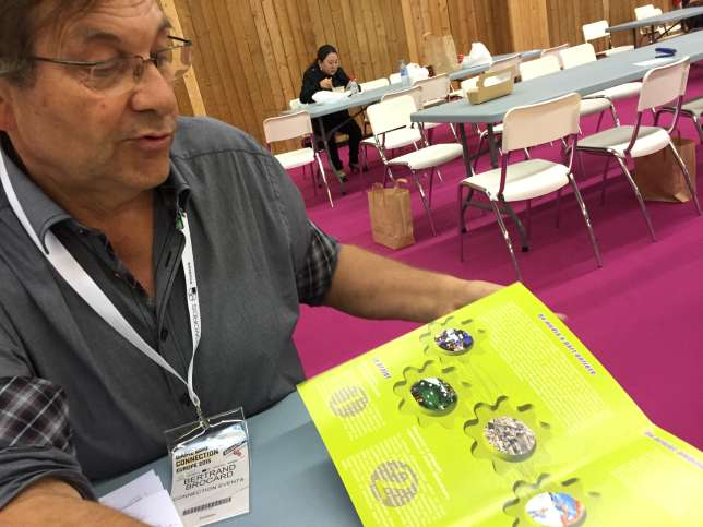 Bertrand Brocard avec une brochure d'époque de la Cité du jeu vidéo.