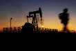 A boy walks by an oil pump at sunset Monday, Jan. 18, 2016, in the desert oil fields of Sakhir, Bahrain. Iran is aiming to increase its oil production by 500,000 barrels per day now that sanctions have been lifted under a landmark nuclear deal with world powers, a top official said. (AP Photo/Hasan Jamali)