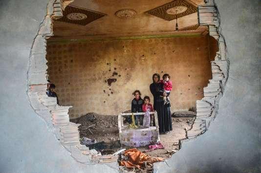 Une femme et ses enfants posent dans les ruines de leur maison détruite par les affrontements entre rebelles kurdes et forces turques, à Silopi (sud-est de la Turquie), le 19 janvier.
