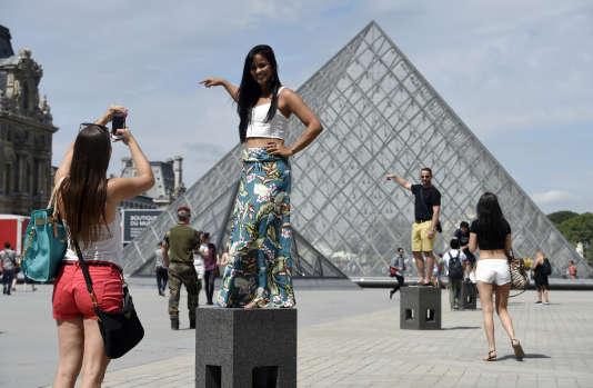 Des touristes se photographient devant la pyramide du Louvre.