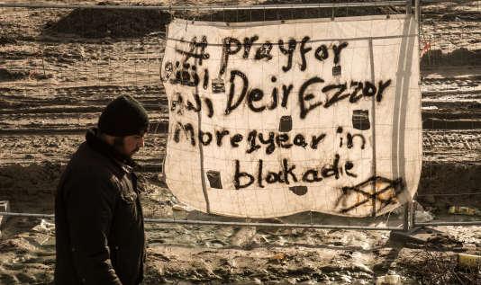 Un homme passe devant une banderole indiquant «Priez pour Deir ez-Zor, sous blocus depuis plus d'un an», dans le camp des migrants de Calais, le 7décembre 2015.