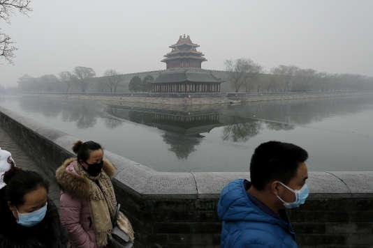 Des passants arborent des masques à proximité d'une des tours d'angle de la Cité interdite, à Pékin, le 8 décembre 2015. Une journée, comme tant d'autres, de forte pollution.