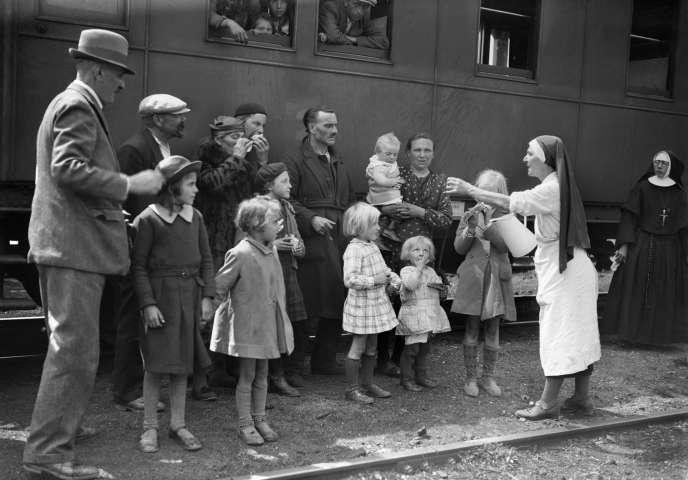 Une infirmière distribue de l'eau à des familles de réfugiés, dans une gare française, en mai 1940, durant la seconde guerre mondiale. / AFP