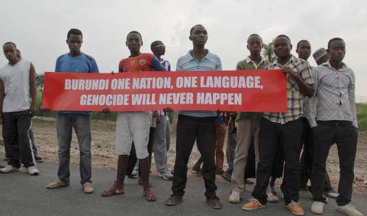 Des jeunes hommes portent une affiche indiquant «Burundi : une seule nation, une seule langue. Le génocide n'aura jamais lieu», sur la route empruntée par la mission du Conseil de sécurité des Nations unies, jeudi 21 janvier 2016, à Bujumbura.