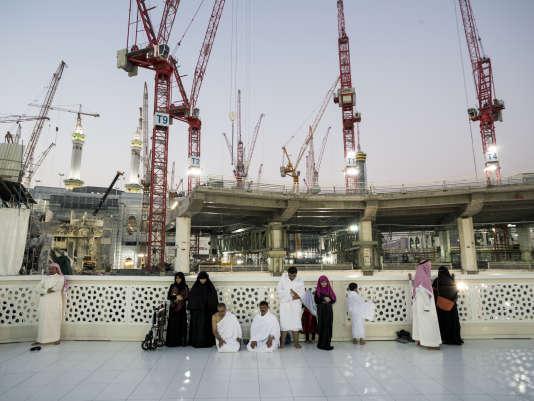 A La Mecque, des fidèles musulmans prient, tandis que des grues travaillent à l'extension du site du pèlerinage, en novembre2013.