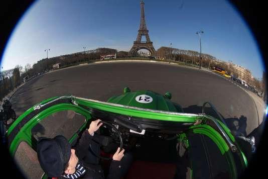 La 2 CV verte et électrique de 4 Roues sous un parapluie face à la tour Eiffel.