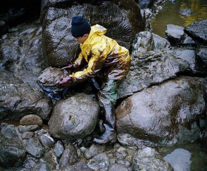 En janvier 2000, un bénévole nettoie  une plage de Vendée touchée  par la marée noire après l'accident de l'«Erika».