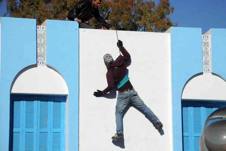 Selon des témoignages, l'homme présent sur cette photo aurait tenté de se suicider avant de recevoir de l'aide, depuis le toit du siège du gouvernorat, pendant les manifestations.