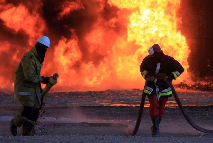 Des ouvriers tentent d'éteindre l'incendie qui ravage un terminal pétrolier de Ras Lanouf, déclenché par des combattants de l'Etat islamique, en Libye, le 21 janvier 2016.