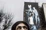 """Téhéran, 8 janvier 2015. Une jeune femme regarde des vielles affiches gouvernementales montrant les """"ennemis""""."""