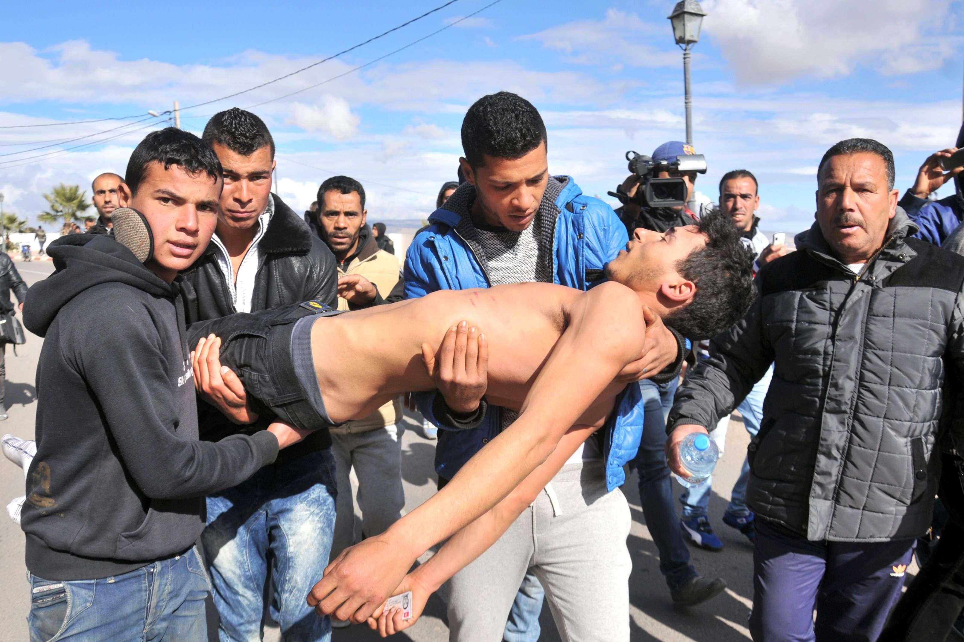 Un jeune homme, présenté comme ayant tenté de mettre fin à ses jours, est transporté afin de recevoir une assistance médicale, à Kasserine, le 22 janvier.