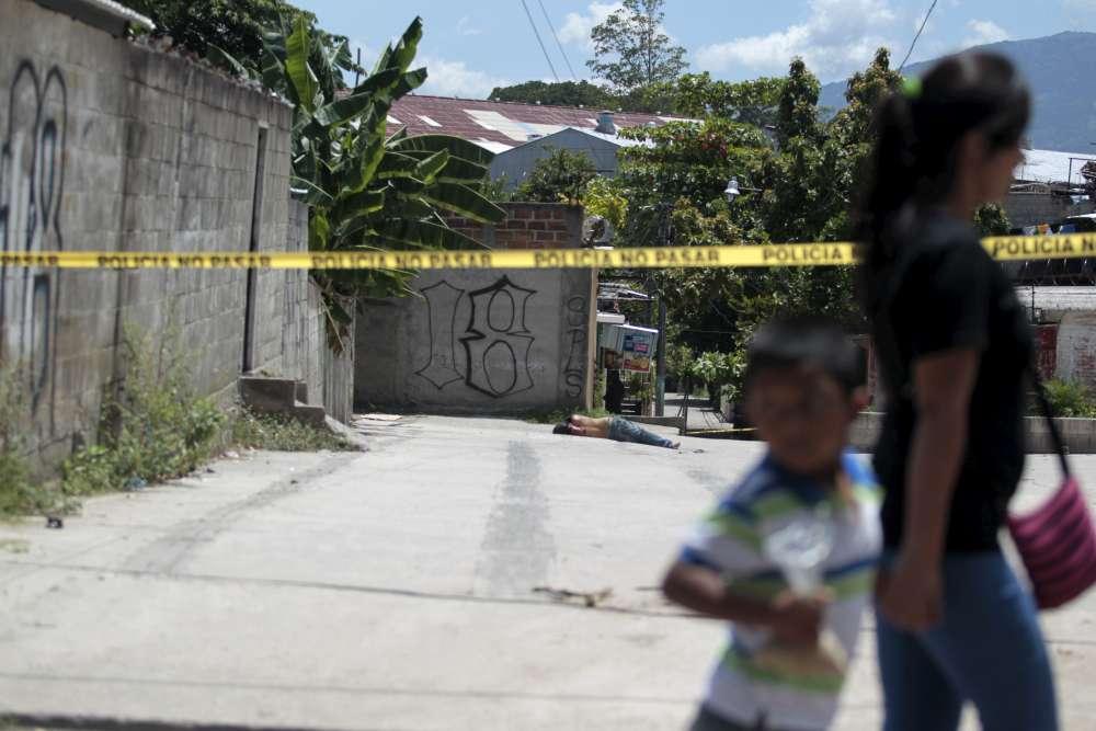 """Une femme et son fils passent devant une scène de crime, où gît un homme tué par balles, dans le quartier de Soyapango, dans la banlieue de San Salvador. L'homme qui a été abattu fait partie du gang """"El Castillo"""", l'un des principaux gangs du pays. « Il y a toujours eu des morts violentes, mais jamais comme maintenant », reconnaît William Hernandez, policier à San Salvador."""