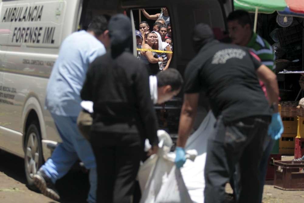 La police scientifique évacue le corps d'un vendeur de pommes de terre abattu sur un marché de La Tiendona, en juillet 2015.