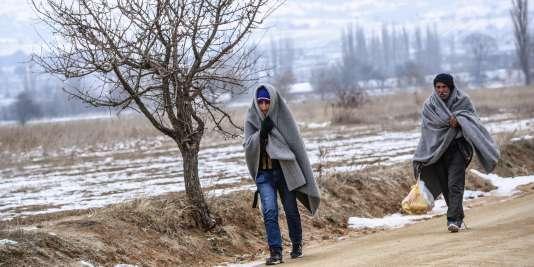 Enveloppés dans des couvertures, des migrants traversent la frontière entre la Serbie et la Macédoine, au niveau du village de Miratovac, le 25 janvier 2016.