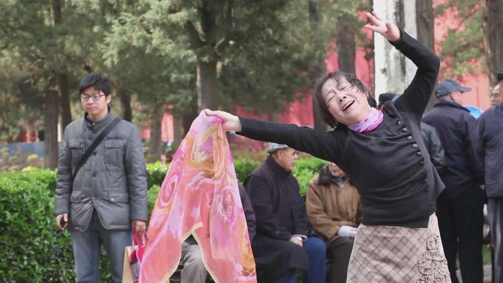 Hu Xiangqian (né en 1983 à Guangdong) filme ici en plan unique une femme qui danse dans un parc de Pékin face à l'indifférence des passants: elle improvise une «chorégraphie légère et gracieuse ».