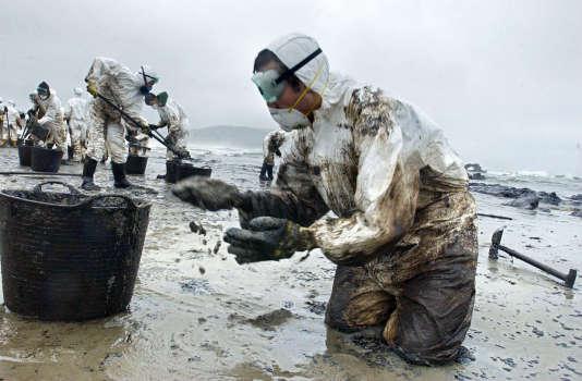 Des bénévoles qui nettoient la plage Nemina, en Espagne, le 1er décembre 2002.