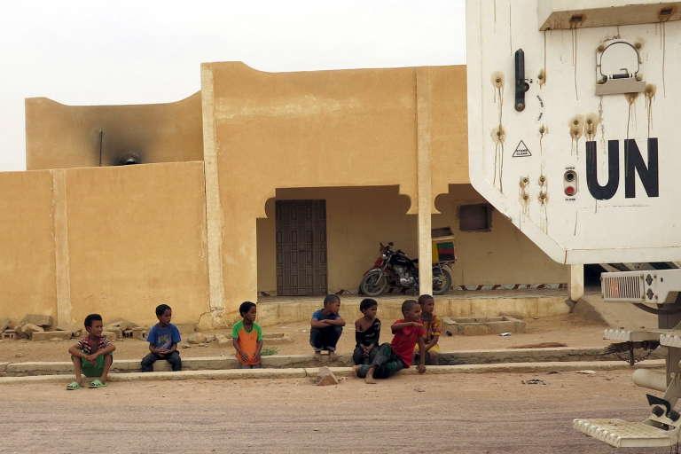 Des enfants regardent passer un véhicule de la Minusma, la force internationale de mission de la paix au Mali, dans les rues de Kidal, au Mali, le 23 juillet 2015.