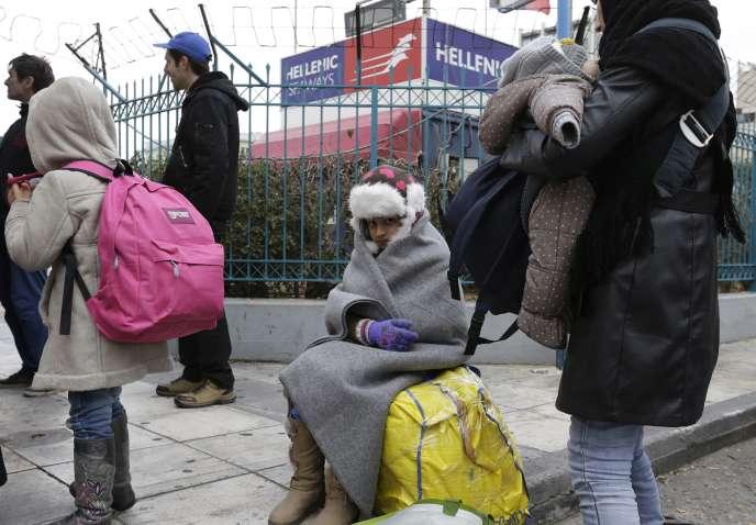Des réfugiés irakiens attendent,  au port du Pirée, le bus qui les conduira vers la frontière avec la Macédoine, lundi 25janvier.