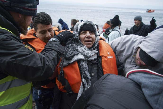 Des volontaires grecs viennent en aide à une femme qui vient de faire la traversée depuis la Turquie jusqu'à l'île grecque de Lesbos, le 26 janvier.